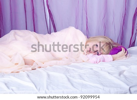 attractive young blond woman laying in her bed