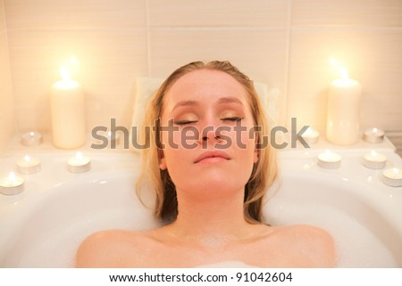 Attractive young blond woman lying in bubble bath with candles (portrait)
