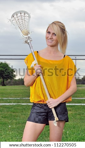 Attractive young blonde female lacrosse player holds the ball in her lacrosse stick - smiling