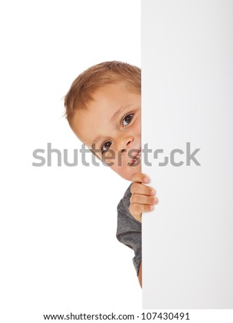 Attractive young boy behind blank white wall. All on white background. - stock photo