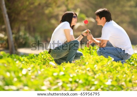 attractive young boy giving beautiful rose to his pretty girlfriend - stock photo
