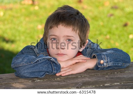 attractive young boy with head over his arms on a wood table