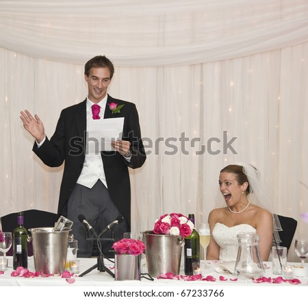 Attractive Young Bride Grimaces At GroomS Speech During Real Wedding Reception Stock Photo
