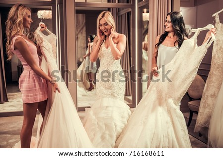 Attractive young bride is smiling while choosing wedding dress in modern wedding salon, girls are showing more dresses #716168611