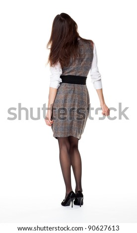 Attractive young brunette businesswoman, rear view, full length portrait; white background