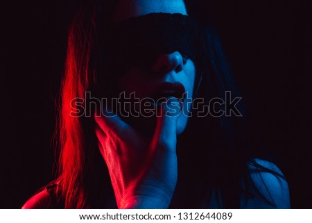 attractive young brunette girl sucks her boyfriend's finger with her mouth lips with a blindfold. The concept of hard sex, BDSM and domination with submission