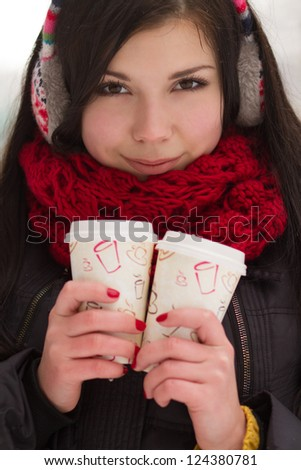 Attractive young brunette holding coffee cups outdoors in a bright winter day