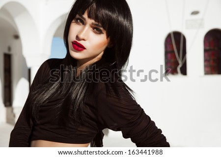 Attractive young brunette in black outfits and shine hair. Bright make up with red lips. Shine straight hair. Sexy female in front of a white building. Santorini day Outdoors shot. horizontal.