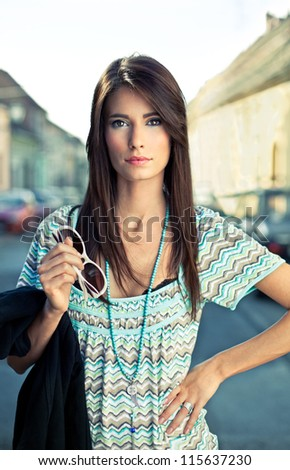 Attractive young brunette posing on the street. Fashion concept.