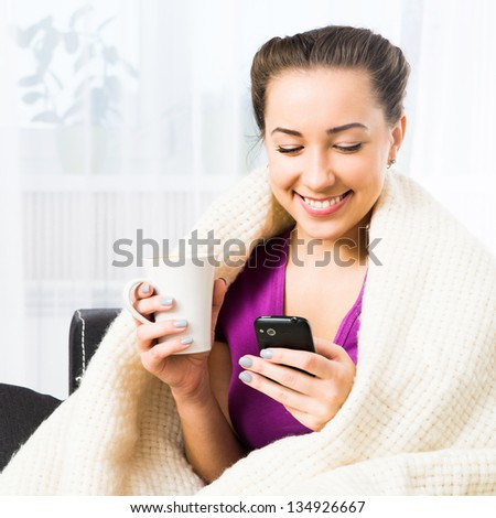 Attractive young brunette woman using her cell phone to send SMS