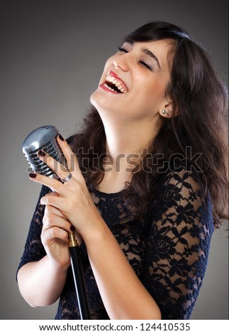 Attractive young brunette woman with a retro microphone
