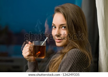 Attractive young brunette woman with mug of hot tea.