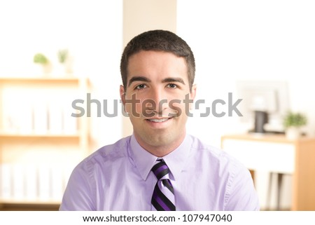 Attractive young business man looking at camera with smile wearing a purple shirt and tie.