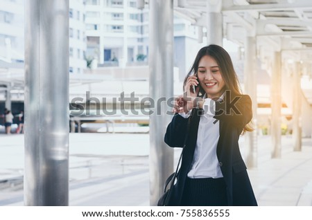 attractive young business woman life style on morning between go to working office with happy and smile talking smartphone with comfortable and good mood relax outdoor concept.