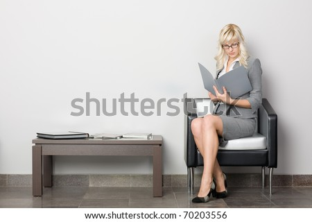 Attractive young business woman sitting in a chair. Waiting room.