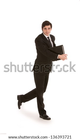 Attractive young businessman in a suit walking with a folder in his hand, full length mid stride studio portrait on white
