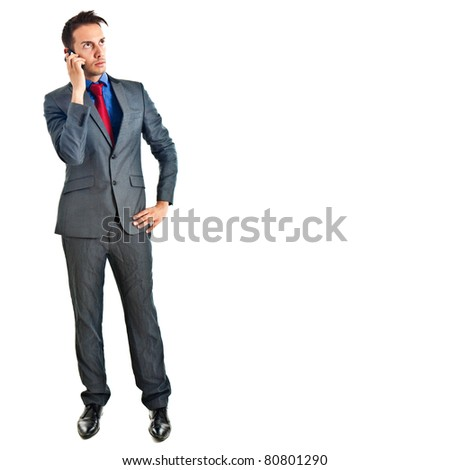 Attractive young businessman on mobile phone against white
