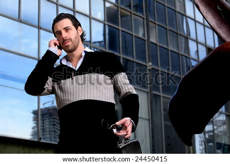 Attractive young businessman using a cell phone in front of a modern office building