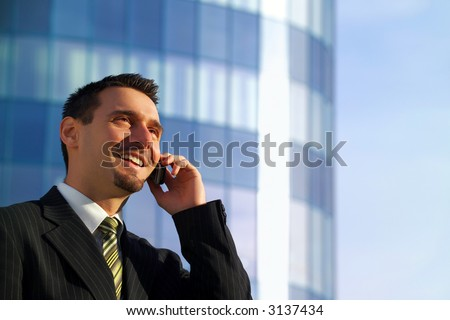 Attractive young businessman using a cell phone in front of a modern office building, smiling