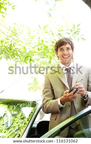 Attractive young businessman using a digital tablet while leaning on the door of his car in a classic city street, smiling.
