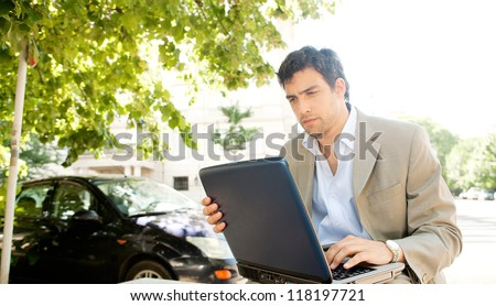 Attractive young businessman using a laptop computer while sitting on a bench in the financial district of a classic city, working outdoors.