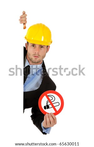 "Attractive young businessman with helmet, behind wall showing ""no smoking"" sign. Copy space. Studio shot. White background."