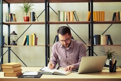 Attractive young businessman with the glasses focused reading book and taking notes at home office