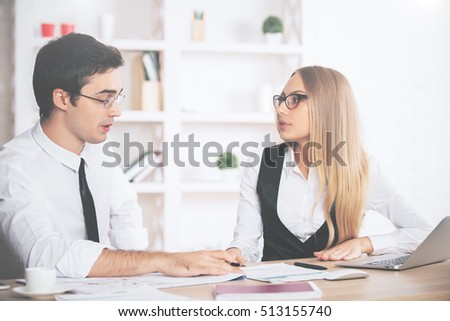 Attractive young businesspeople in formal outfits doing paperwork in modern office. Team work concept - Shutterstock ID 513155740