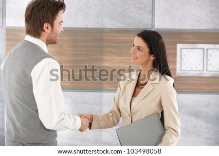 Attractive young businesspeople shaking hands in modern office, smiling.