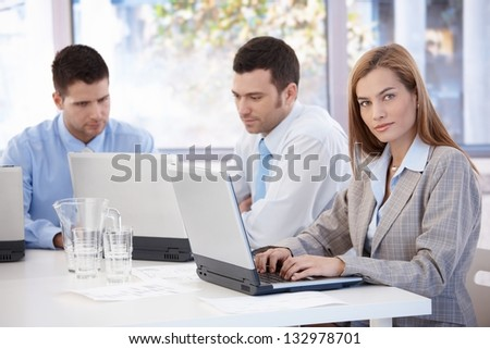 Attractive young businesswoman and colleagues working in meeting room.