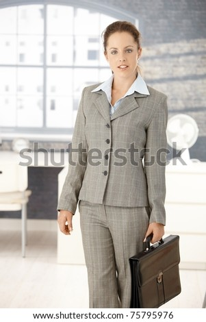 Attractive young businesswoman arriving to office in the morning, holding briefcase.?