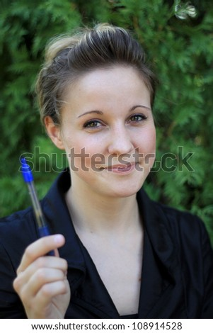 Attractive Young Businesswoman Holding a Pen Smiling