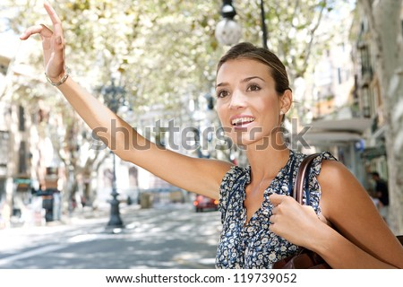 Attractive young businesswoman raising her arm to call a taxi in a busy city, outdoors.