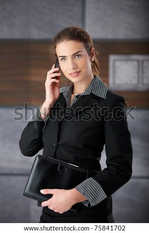 Attractive young businesswoman talking on mobile phone.?