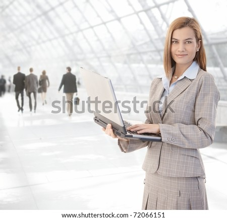 Attractive young businesswoman using laptop at office lobby, smiling.?