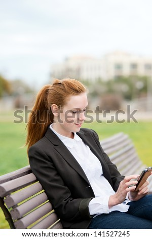 Attractive young businesswoman using smartphone while sitting in city park bench