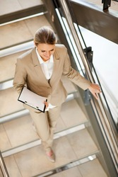 attractive young businesswoman walking down stairs
