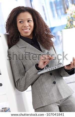 Attractive young businesswoman working on laptop, smiling.