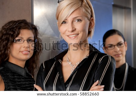 Attractive young businesswomen, waiting for lift in office lobby, talking.