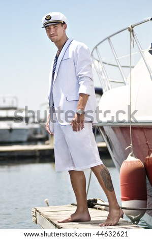 Attractive young captain over the jetty beside his boat