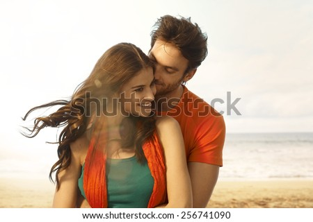 Attractive young casual caucasian brunette woman getting a kiss from boyfriend at beach. Romance, couple, smiling, embracing. Lens flare, sand and copyspace.