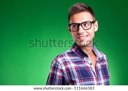 Attractive young casual man wearing glasses and looking away, against green background
