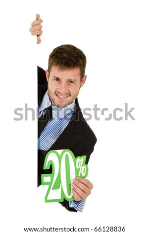Attractive young caucasian businessman behind a wall showing twenty percent discount sign. Copy space. Studio shot. White background.