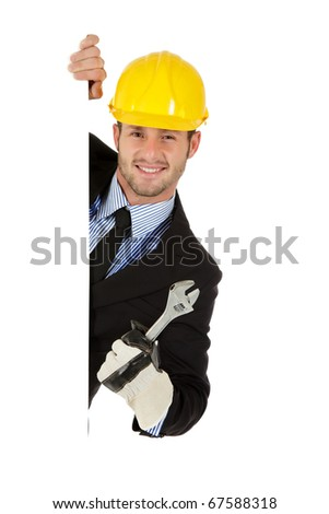 Attractive young caucasian businessman behind wall equipped with protective glove and helmet  holding a plumber spanner. Copy space. Studio shot. White background.