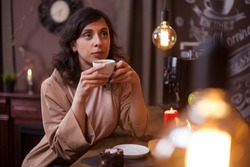 Attractive young caucasian woman drinking coffee in a coffee shop at the bar counter. Happu customer in a coffee shop. Young caucasian woman enjoying a coffe in a coffee shop.