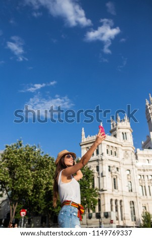 attractive young cheerful woman taking a selfie in Madrid, Spain #1149769337