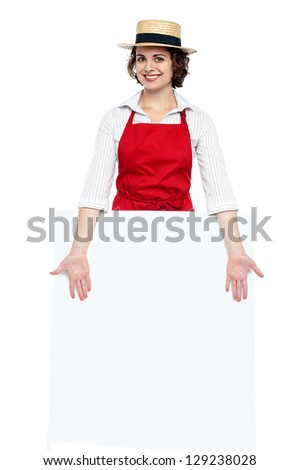 Attractive young chef presenting blank whiteboard. Ad concept.