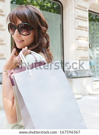 Attractive young consumer woman walking down a shopping avenue with elegant buildings and stores, carrying paper bags during a fun and sunny day, turning to smile at the camera.