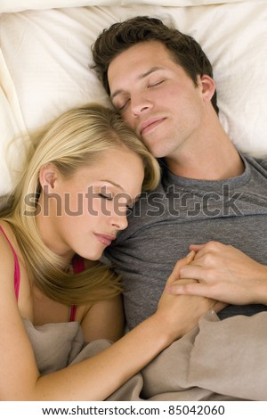 Attractive young couple asleep in bed
