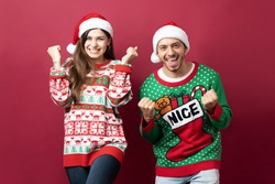 Attractive young couple celebrating some great news while wearing ugly sweaters for Christmas